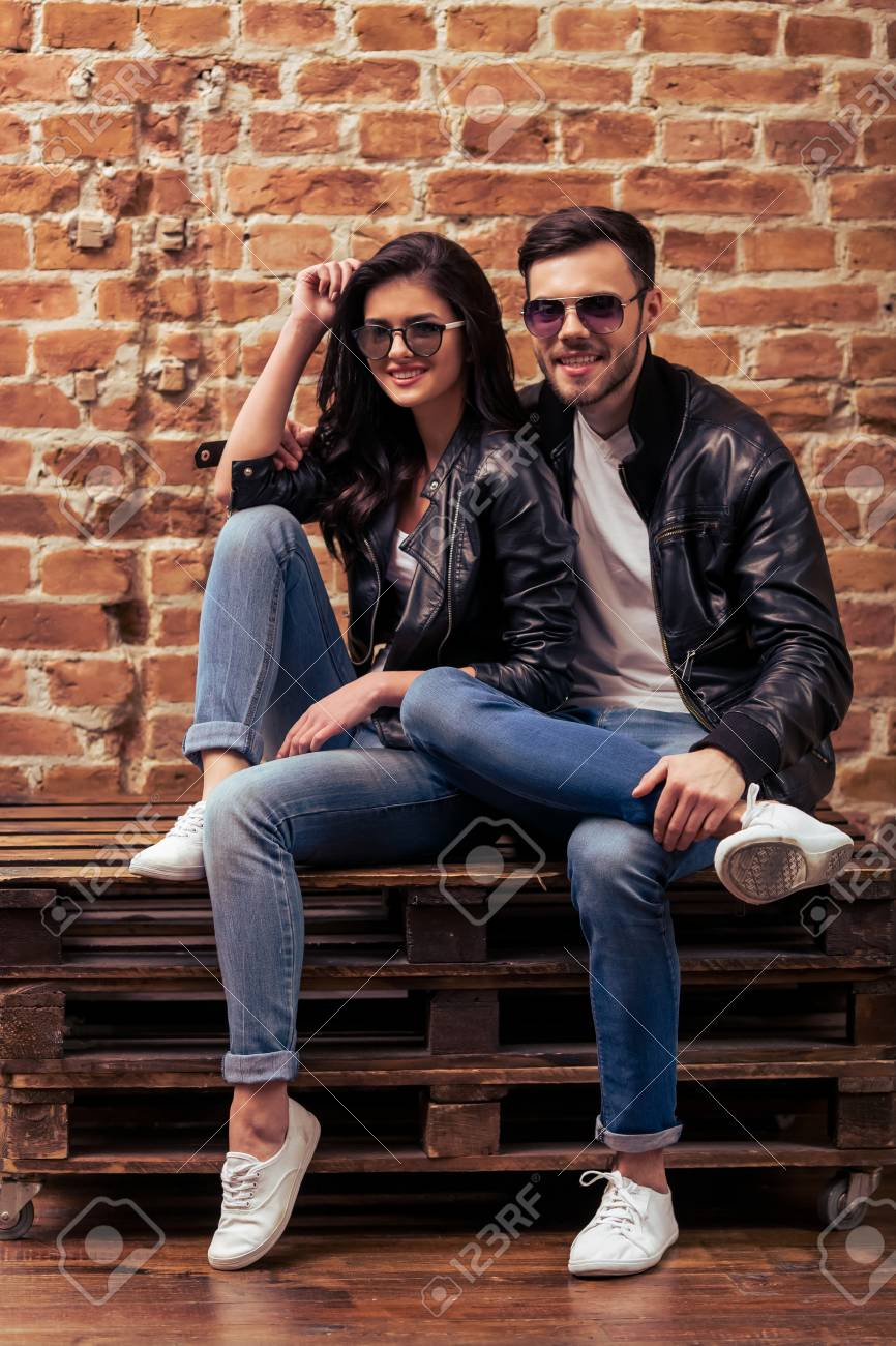 Cool Beautiful Young Couple In Leather Jackets And Sunglasses Is Looking At Camera And Smiling