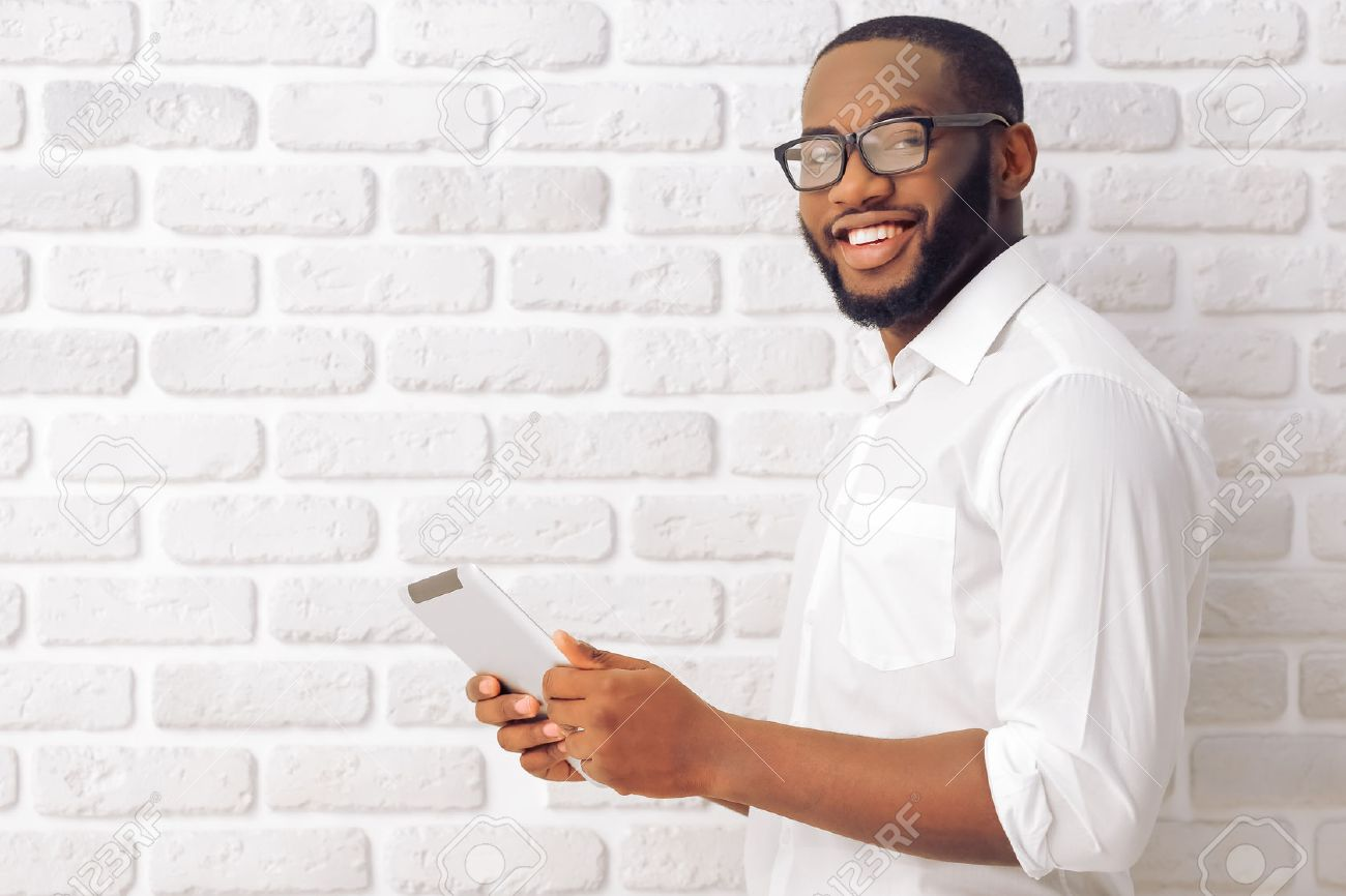Side view of Afro American man in classic shirt and glasses using a tablet, looking at camera and smiling, standing against white brick wall - 53992354