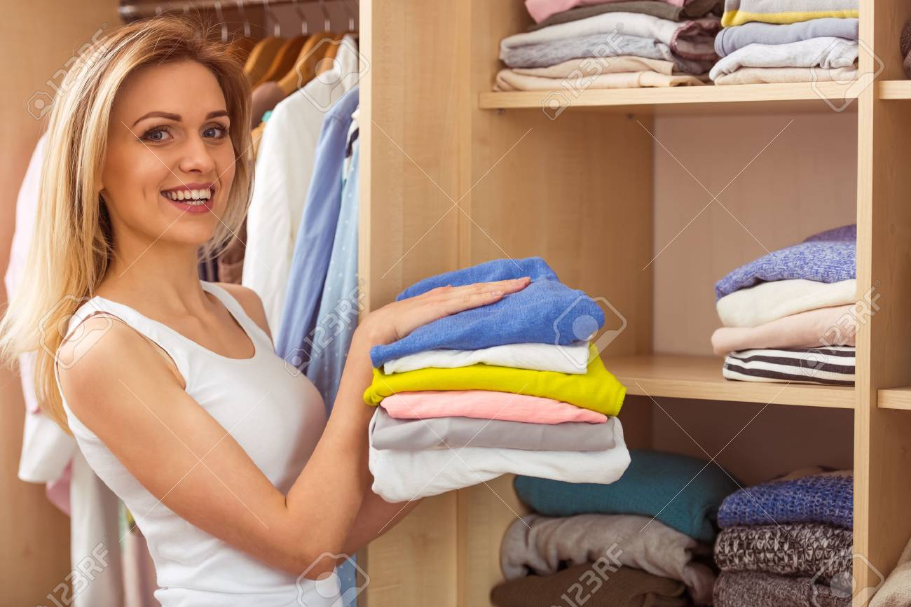 Beautiful Girl Is Smiling And Looking At Camera While Putting Clothes In A  Wardrobe Stock Photo