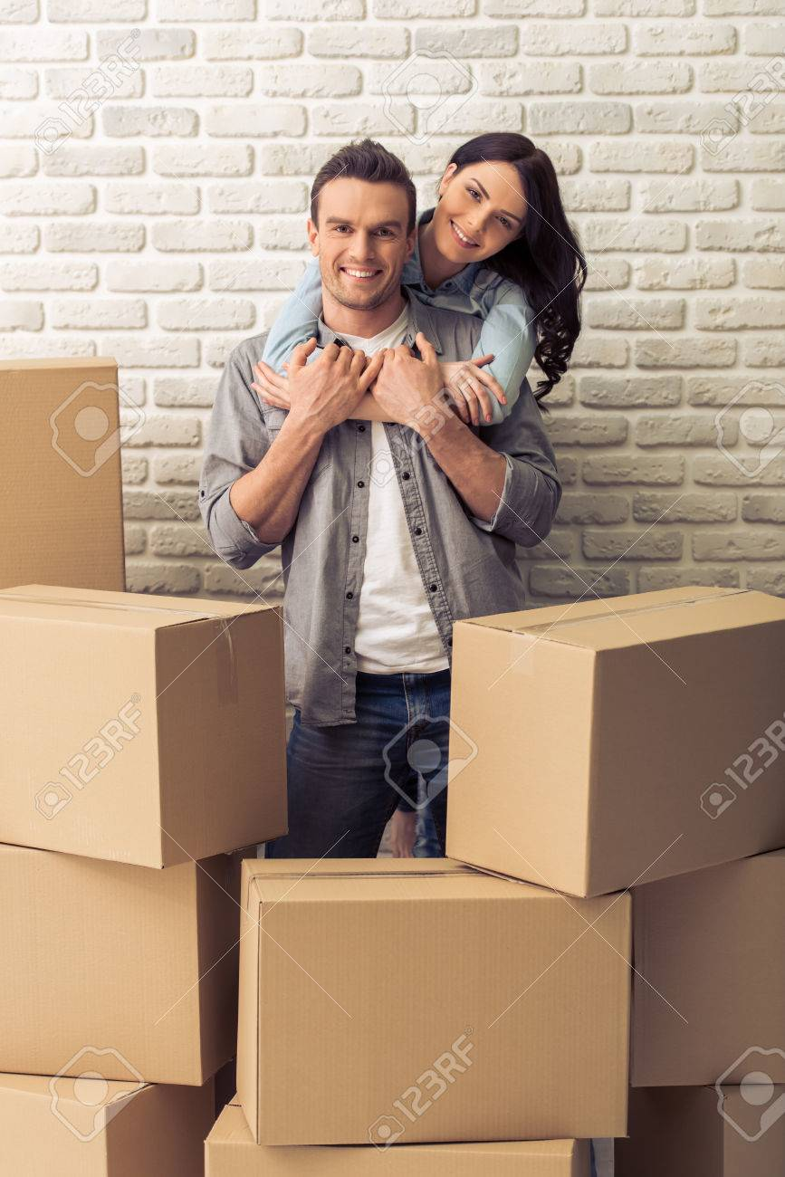 Happy Young Couple Is Moving, Cuddling, Looking At Camera And ... on romantic bedroom ideas, young couple bedding, master bedroom ideas, couple bedroom wall decorating ideas, young woman's bedroom ideas, young couple home ideas, young couple wallpaper, adult bedroom wall decor ideas, diy teen bedroom ideas, young couple house decorating ideas, cheetah print bedroom ideas, narrow bedroom ideas, small bathroom decorating ideas, young couples apartment bedroom, young couple living room, hipster bedroom ideas, couples apartment bedroom ideas, sexy bedroom ideas, young women bedroom ideas, couple bedroom design ideas,