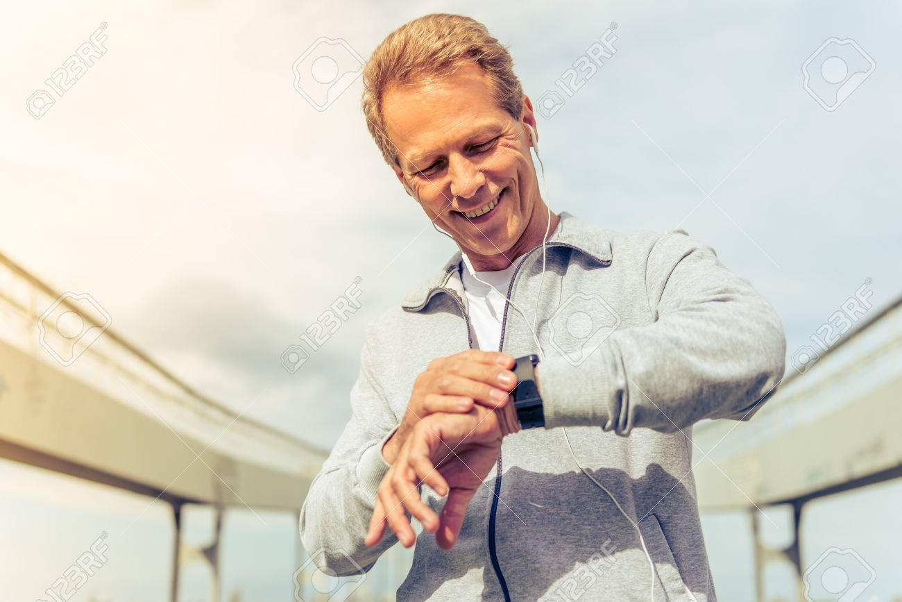 Handsome middle aged man in sports uniform and headphones is looking at his watch and smiling during morning run - 57413791