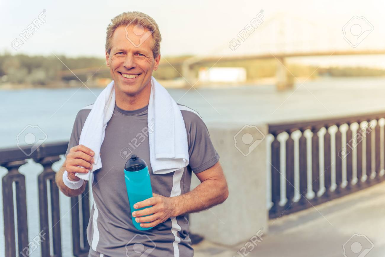 Handsome middle aged man in sports uniform is holding a bottle of water, looking at camera and smiling, resting during morning run - 57413815