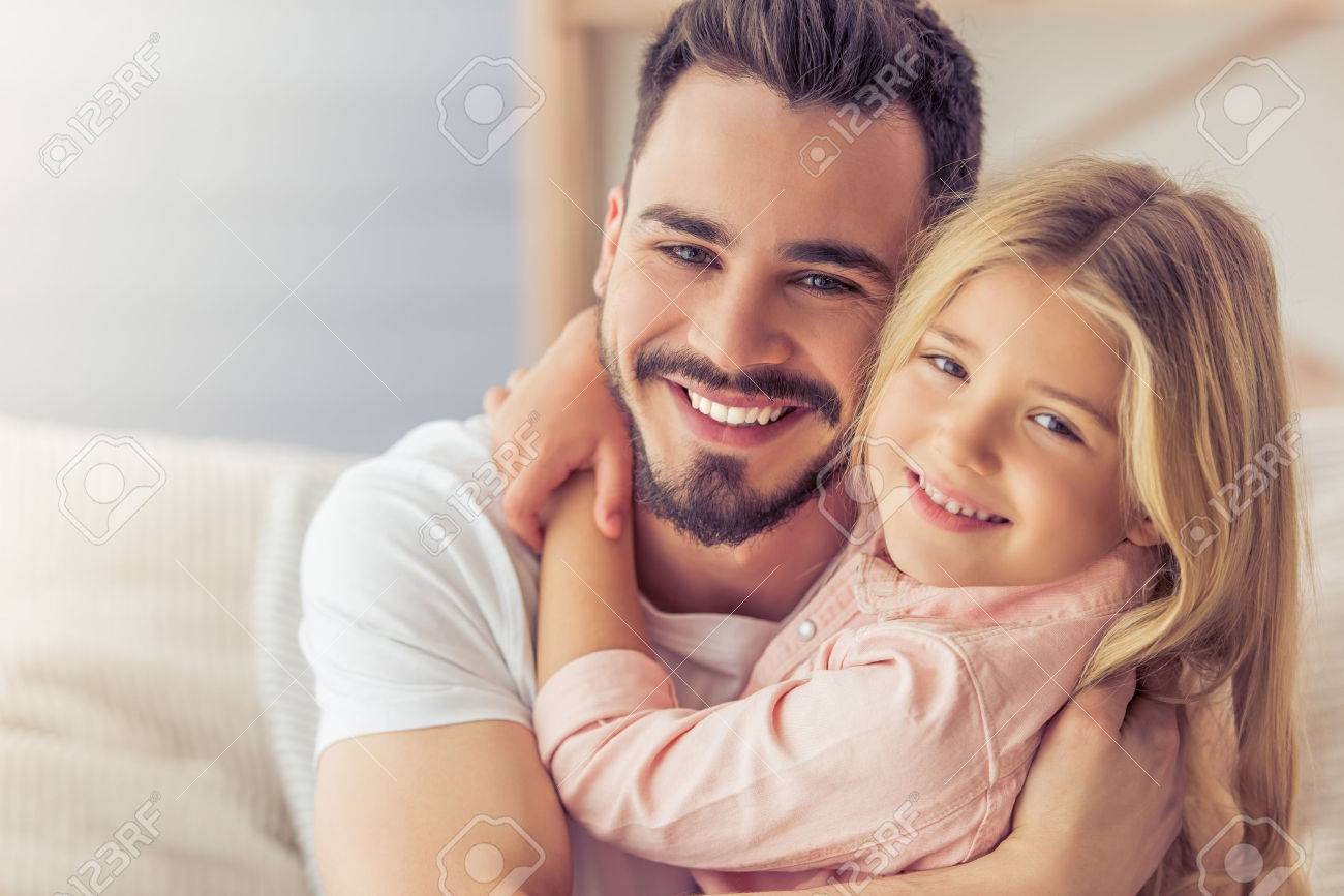 Portrait of handsome father and his cute daughter hugging, looking at camera and smiling - 57830602