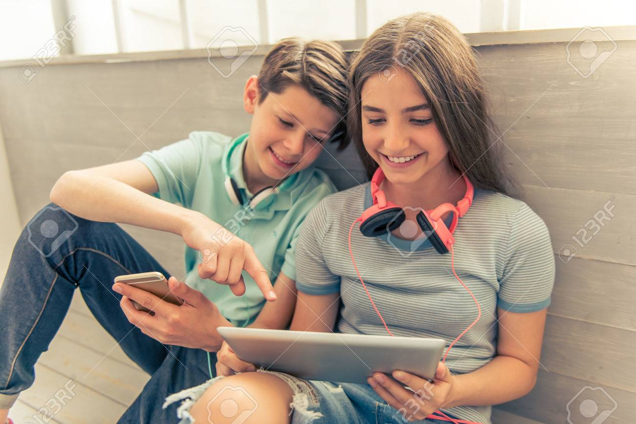 Teenage boy and girl with headphones are using gadgets, talking and smiling while sitting on the floor - 58684634