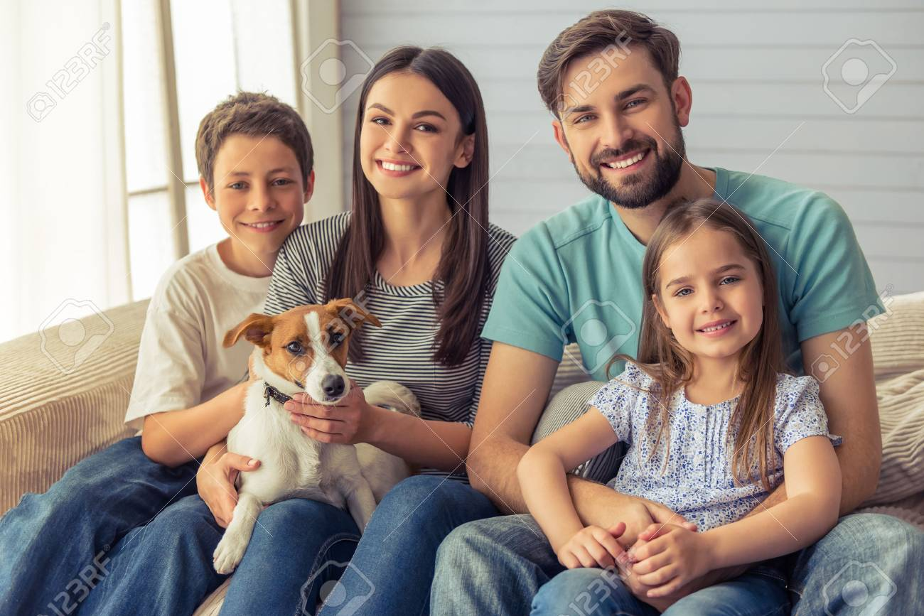 Beautiful young parents, their cute little daughter and son are looking at camera and smiling, sitting with their cute dog on sofa at home - 58804659