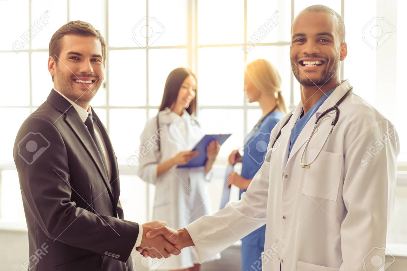 Handsome businessman and Afro American doctor are shaking their hands, looking at camera and smiling, two female doctors are talking in the background - 58989970