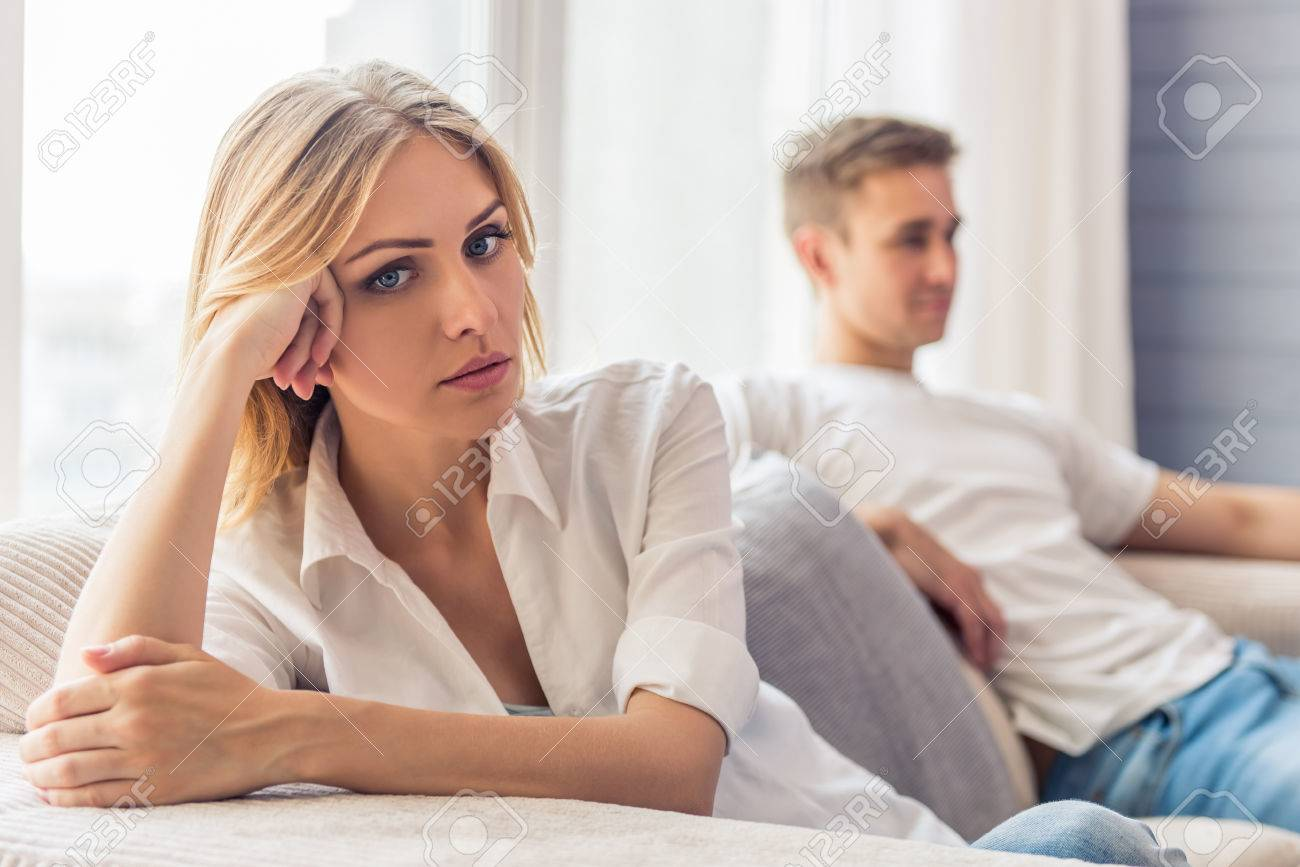 Young couple quarrels. Beautiful young woman is sitting sad on couch at home, her boyfriend is sitting in the background - 60114184