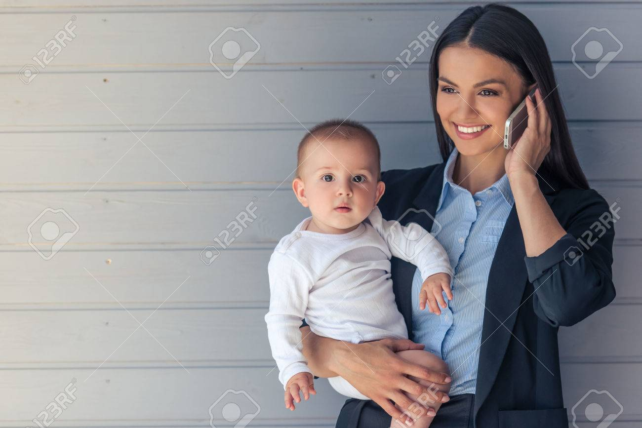 Portrait of beautiful business lady in classic suit and her sweet little baby on gray background. Mom is talking on the mobile phone and smiling, baby is looking at camera - 61008468