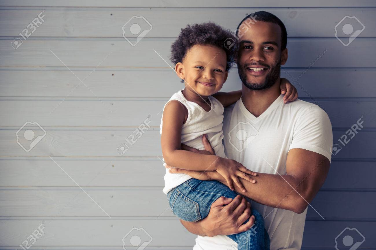Portrait of handsome young Afro American father and his cute child hugging, looking at camera and smiling - 61557227