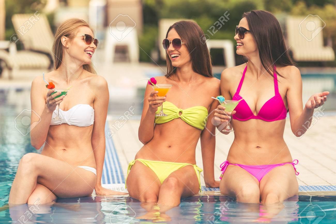 d5b40b426b5a Hermosas chicas en traje de baño y gafas de sol están hablando, bebiendo  cócteles y sonriendo mientras toma el sol cerca de la piscina