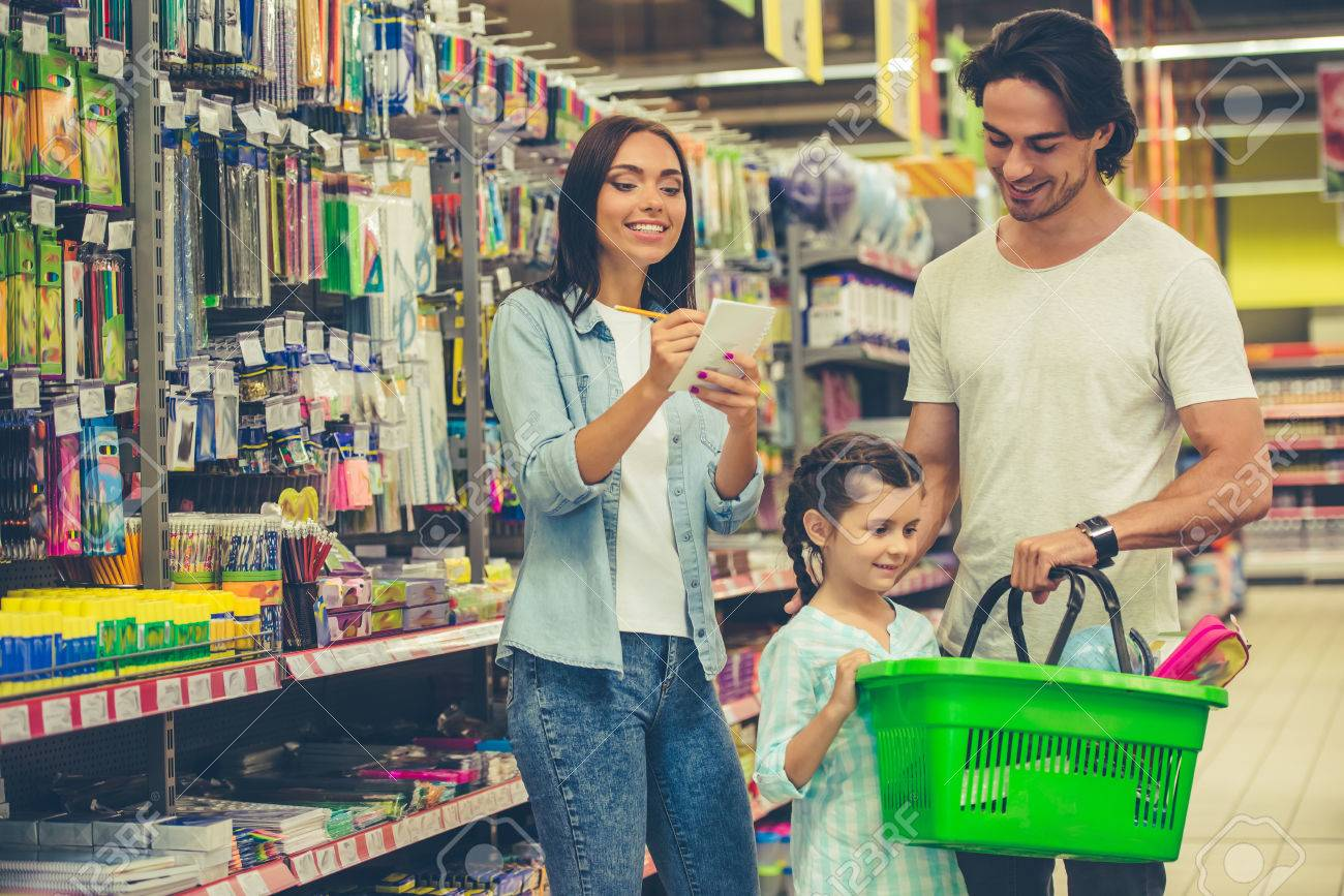 Beautiful young parents and their cute little daughter are smiling while choosing school stationery in the supermarket. Mom is making notes in the list - 62528349