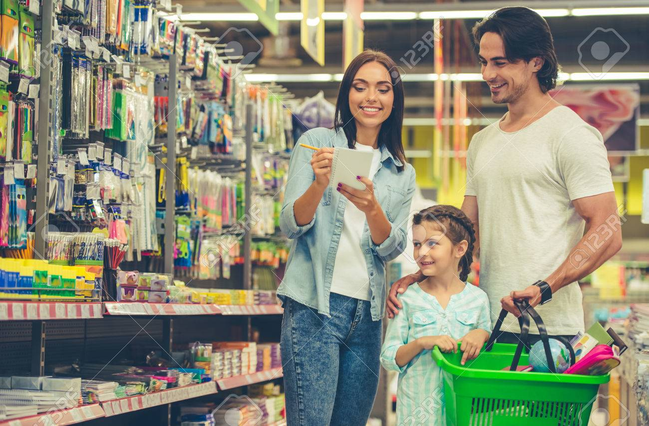 Beautiful young parents and their cute little daughter are smiling while choosing school stationery in the supermarket. Mom is making notes in the list - 62528285