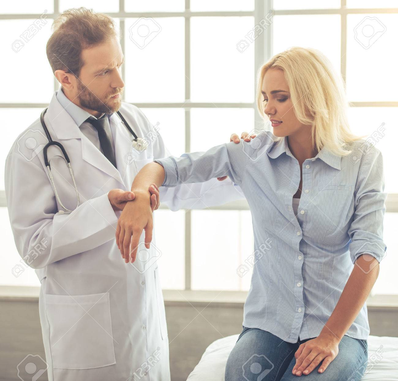 Handsome doctor is examining female patient's injured hand while working in his office - 64005749