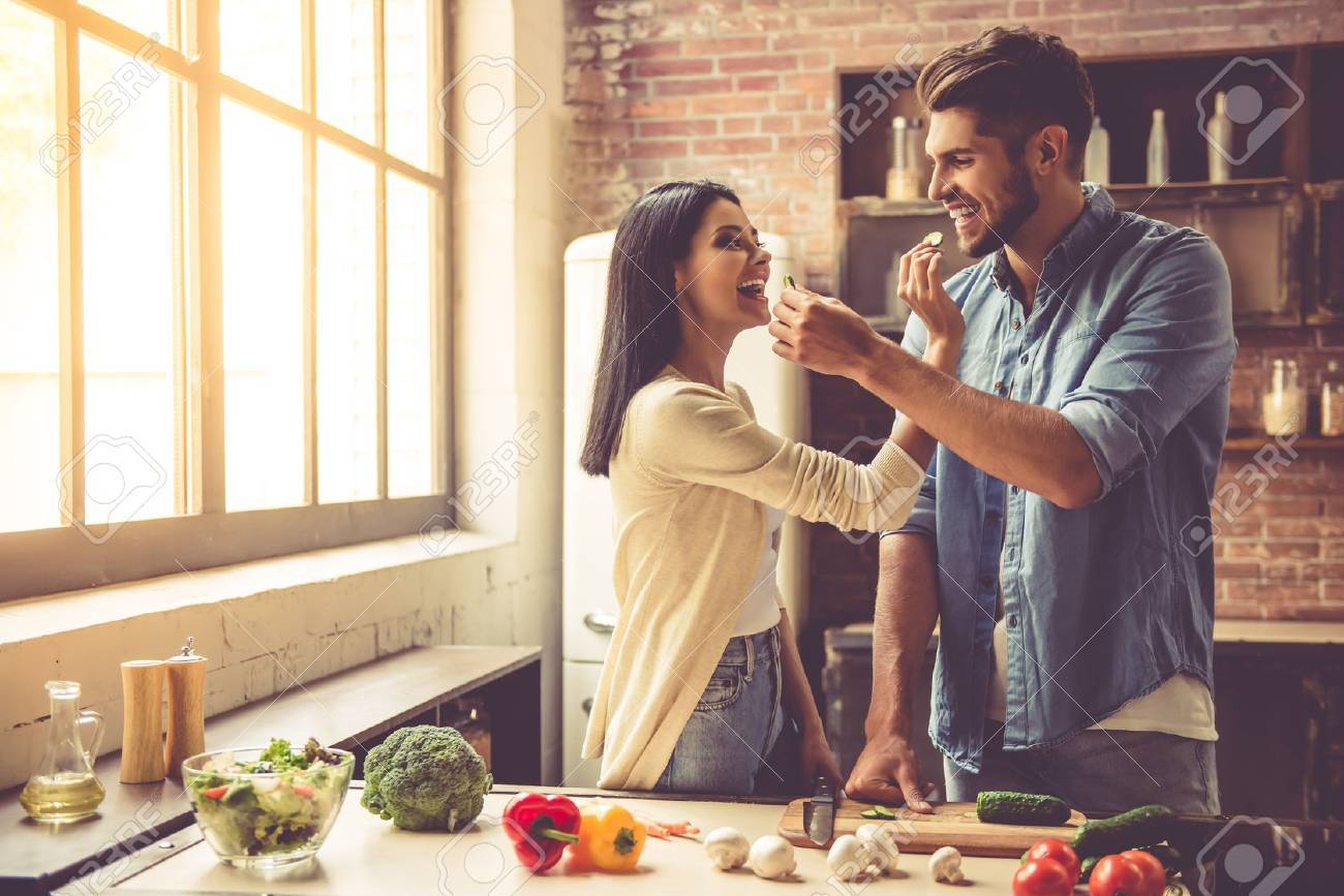 Beautiful young couple is feeding each other and smiling while cooking in kitchen at home - 64346720