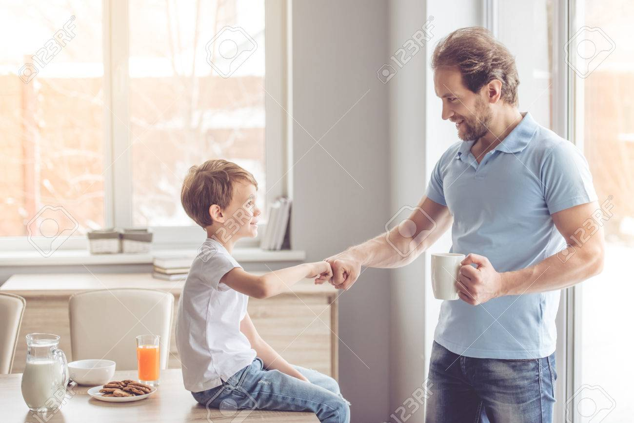Father and son are giving five and smiling while having a snack in kitchen - 66198012