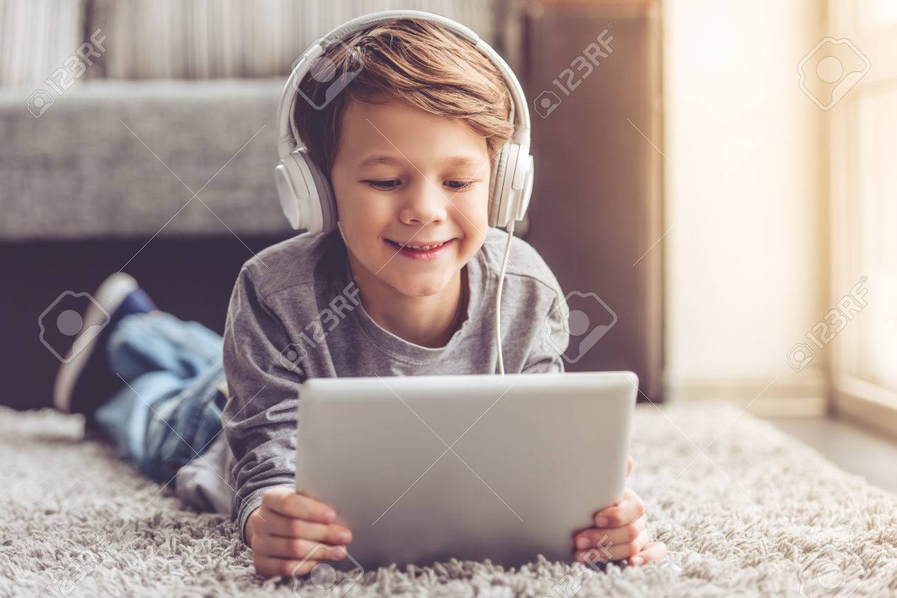 Little boy in headphones is using a digital tablet and smiling while lying on the floor at home - 66198019
