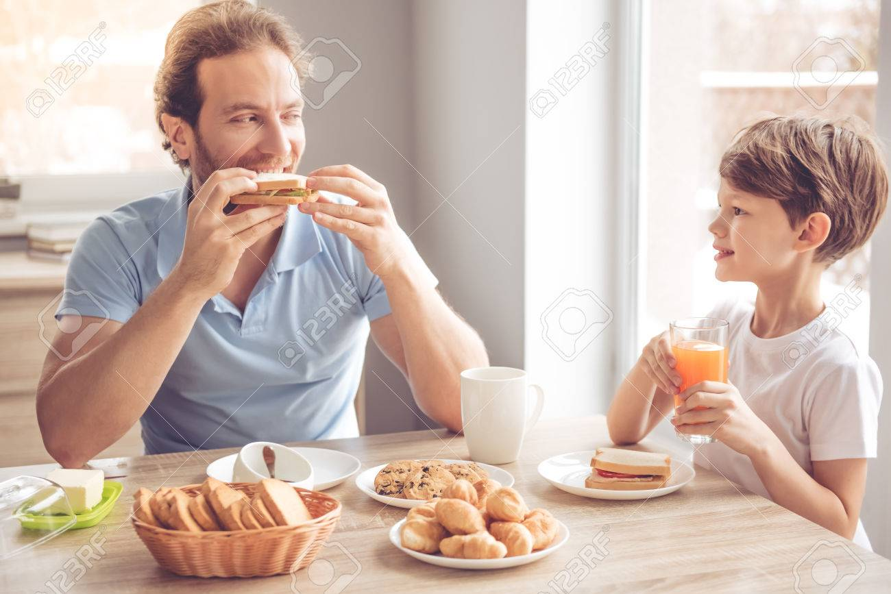 Father and son are talking and smiling while having a breakfast in kitchen - 66197535