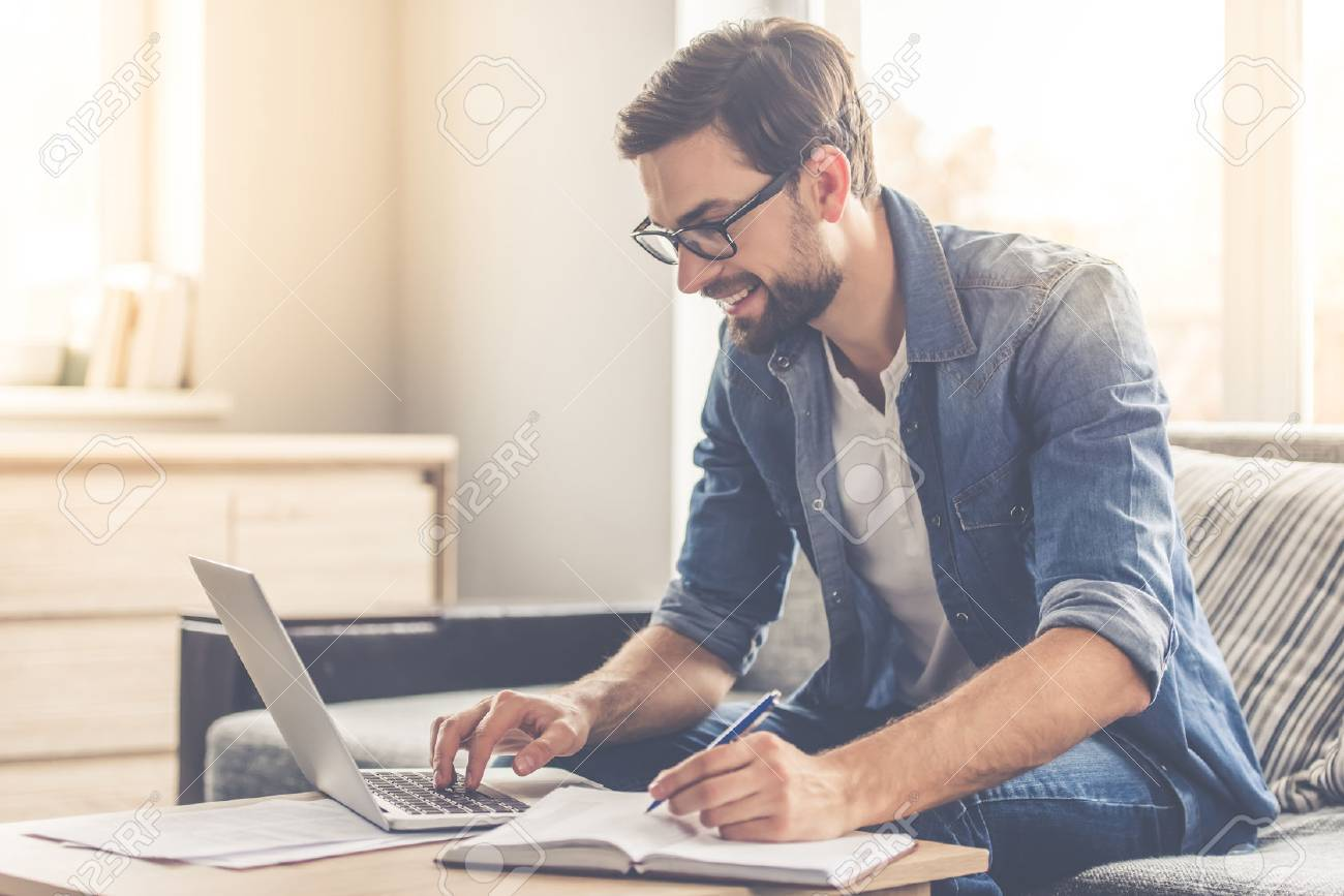 Handsome businessman in eyeglasses is making notes and smiling while working with a laptop at home - 66449770