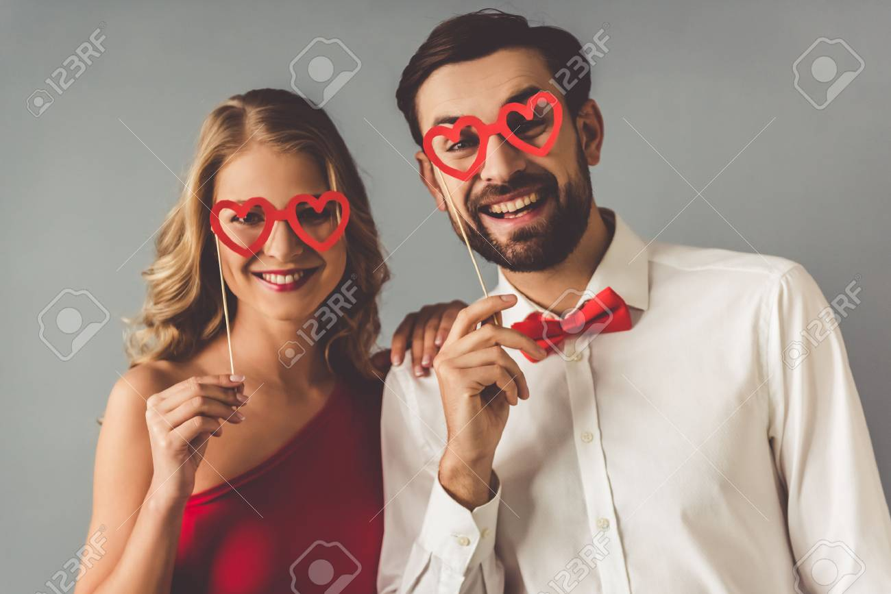 Beautiful elegant girl in red dress and guy in classic shirt and red bow tie are holding a paper heart glasses and smiling, on gray background - 66793477