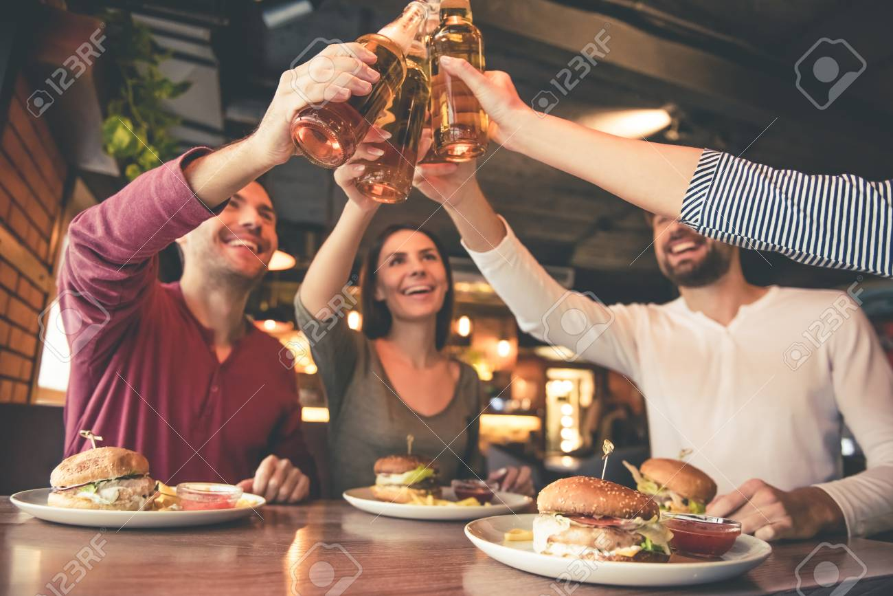 Happy friends are clinking bottles and smiling while spending time together in cafe - 68932907