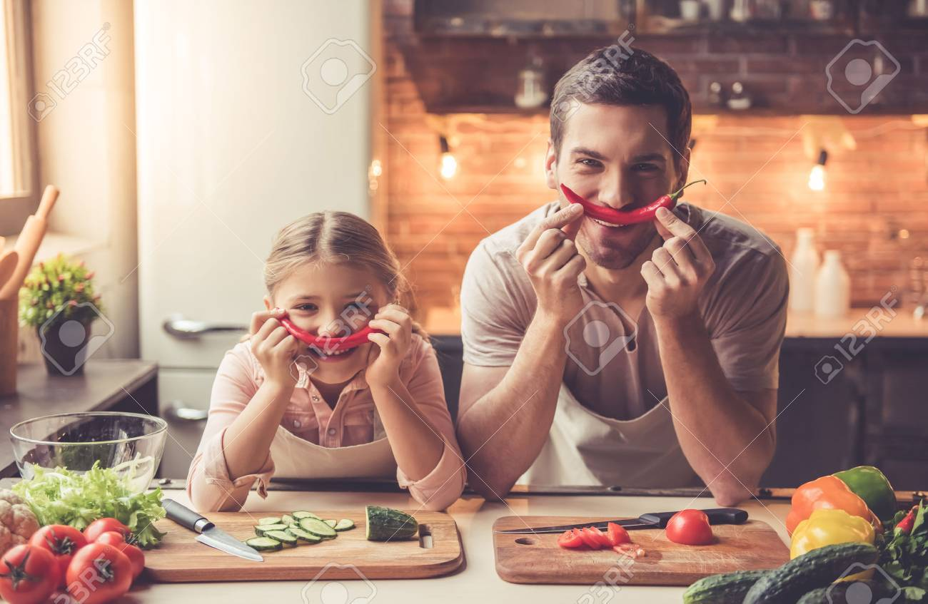 Cute little girl and her handsome dad are holding pepper and smiling while cooking in kitchen at home - 69038046