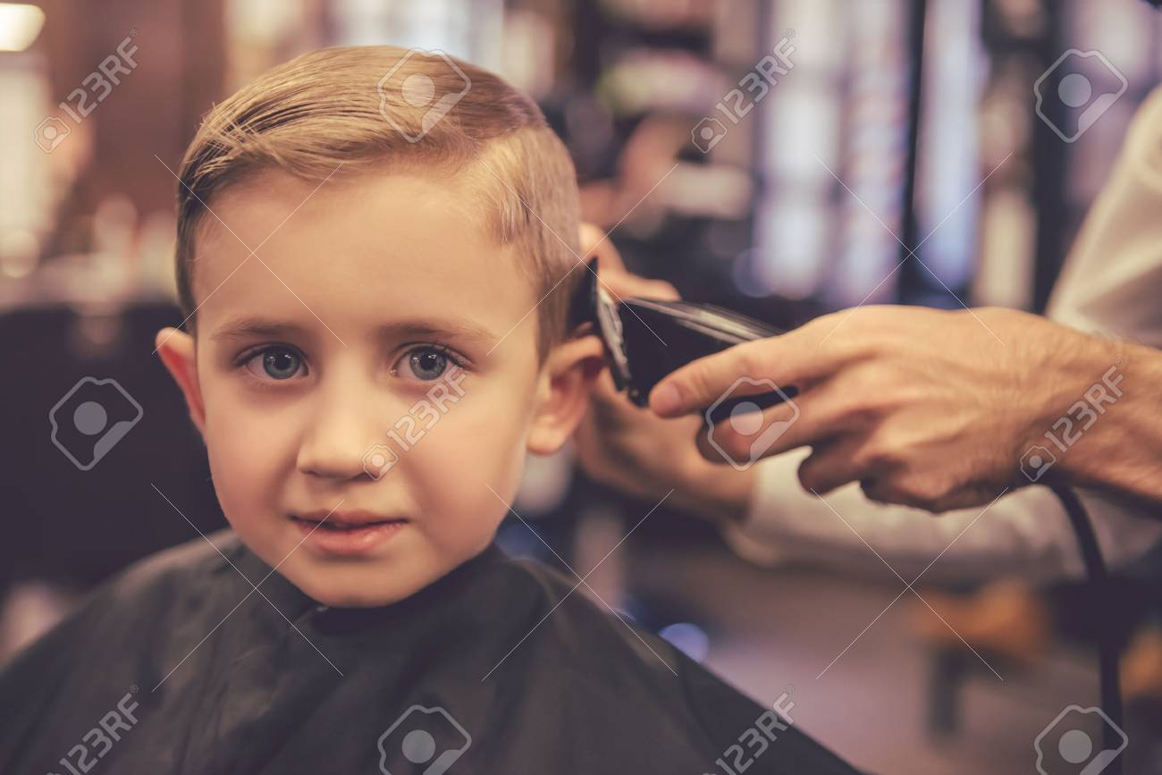 Cute Little Boy Is Looking At Camera While Getting Haircut By