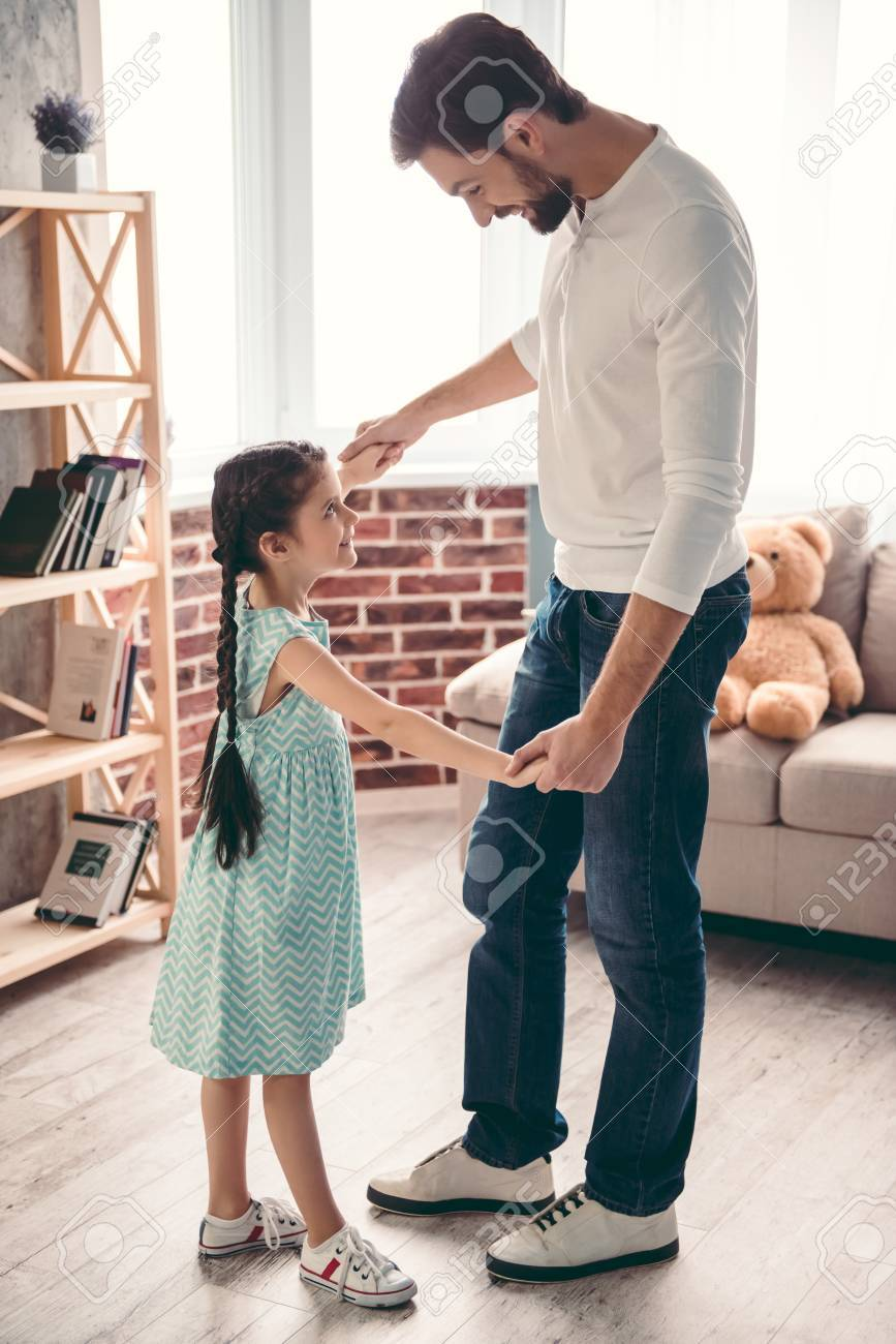 Cute little girl and her handsome father are smiling while dancing together at home - 70041162