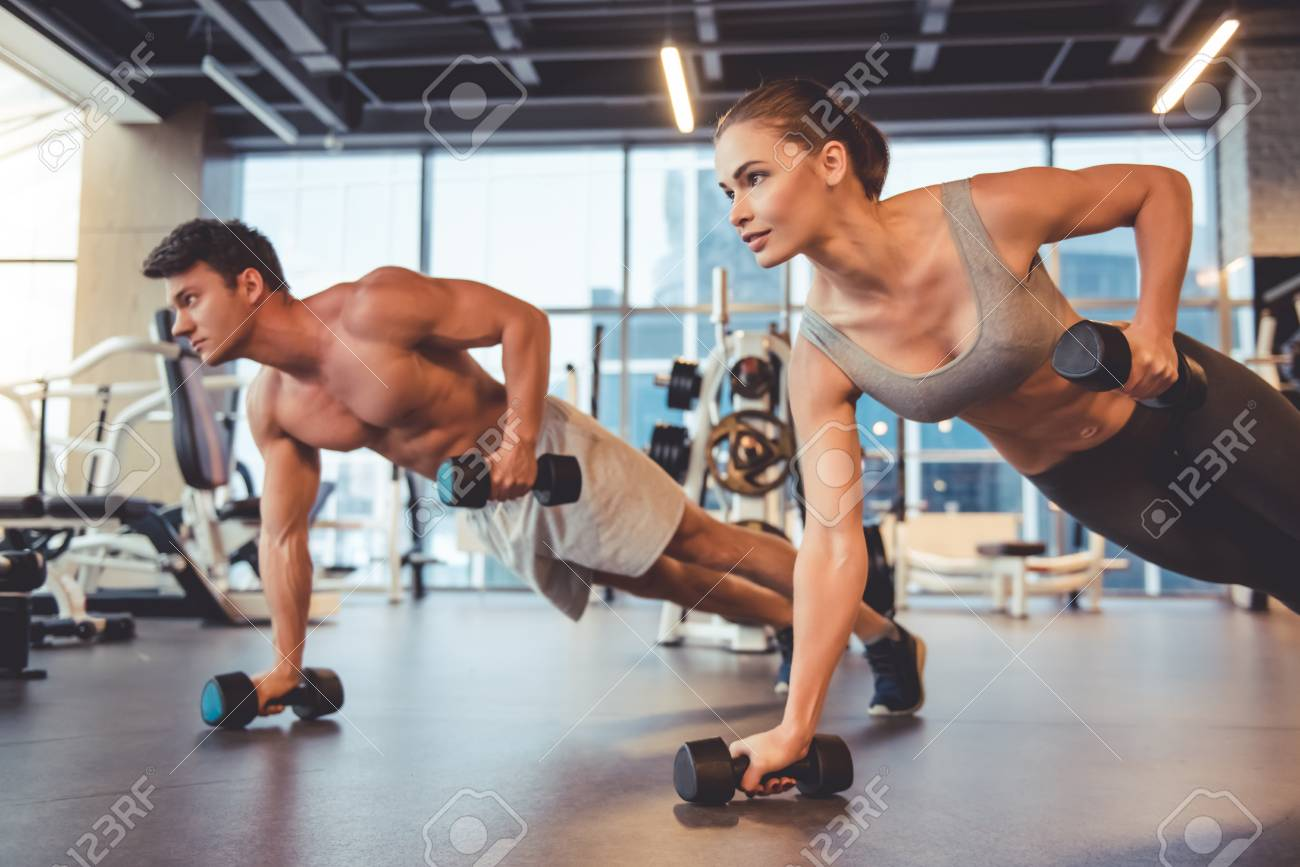 Attractive young sports people are working out with dumbbells in gym - 70653995