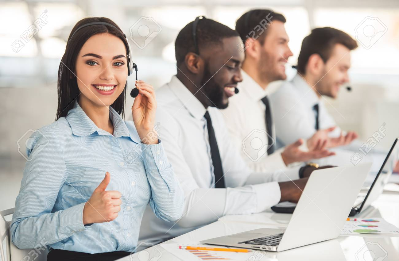 Attractive Business People In Suits And Headsets Are Smiling