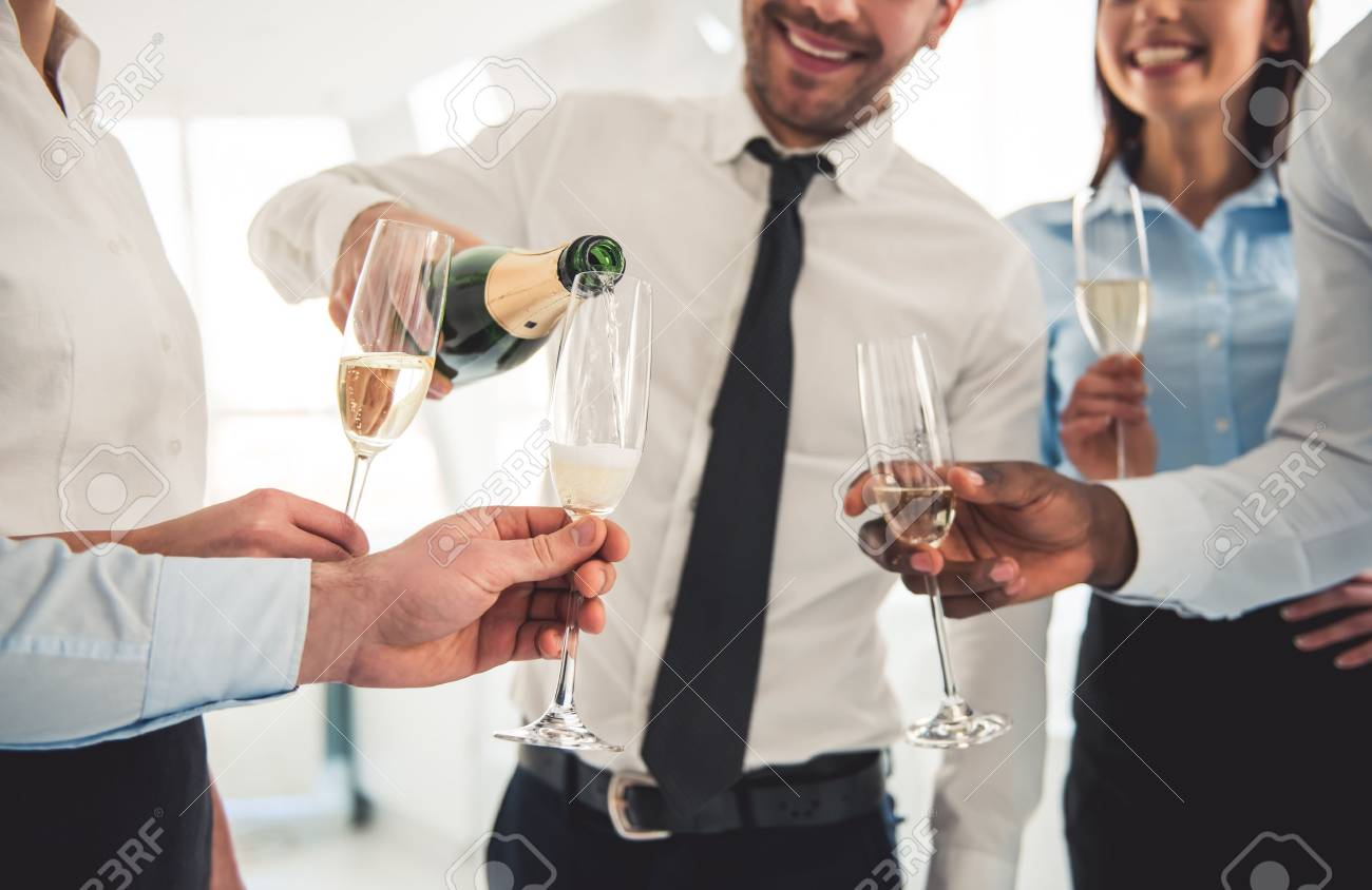 Cropped image of successful business people drinking champagne, talking and smiling while celebrating in office - 71669271