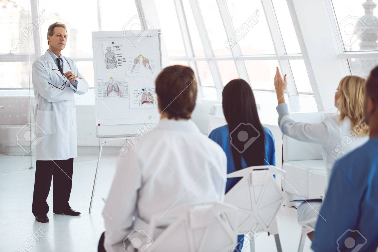 Handsome mature medical doctor is giving lecture for his colleagues using a whiteboard and schemes - 72129905