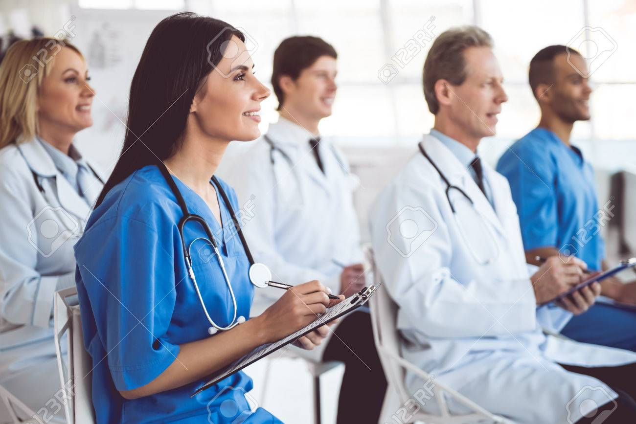 Successful medical doctors are making notes and smiling while sitting at the conference - 72129967