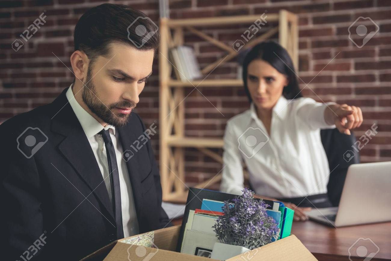 Getting fired. Handsome businessman in suit is holding a box with his stuff, woman in the background is pointing away - 72680907
