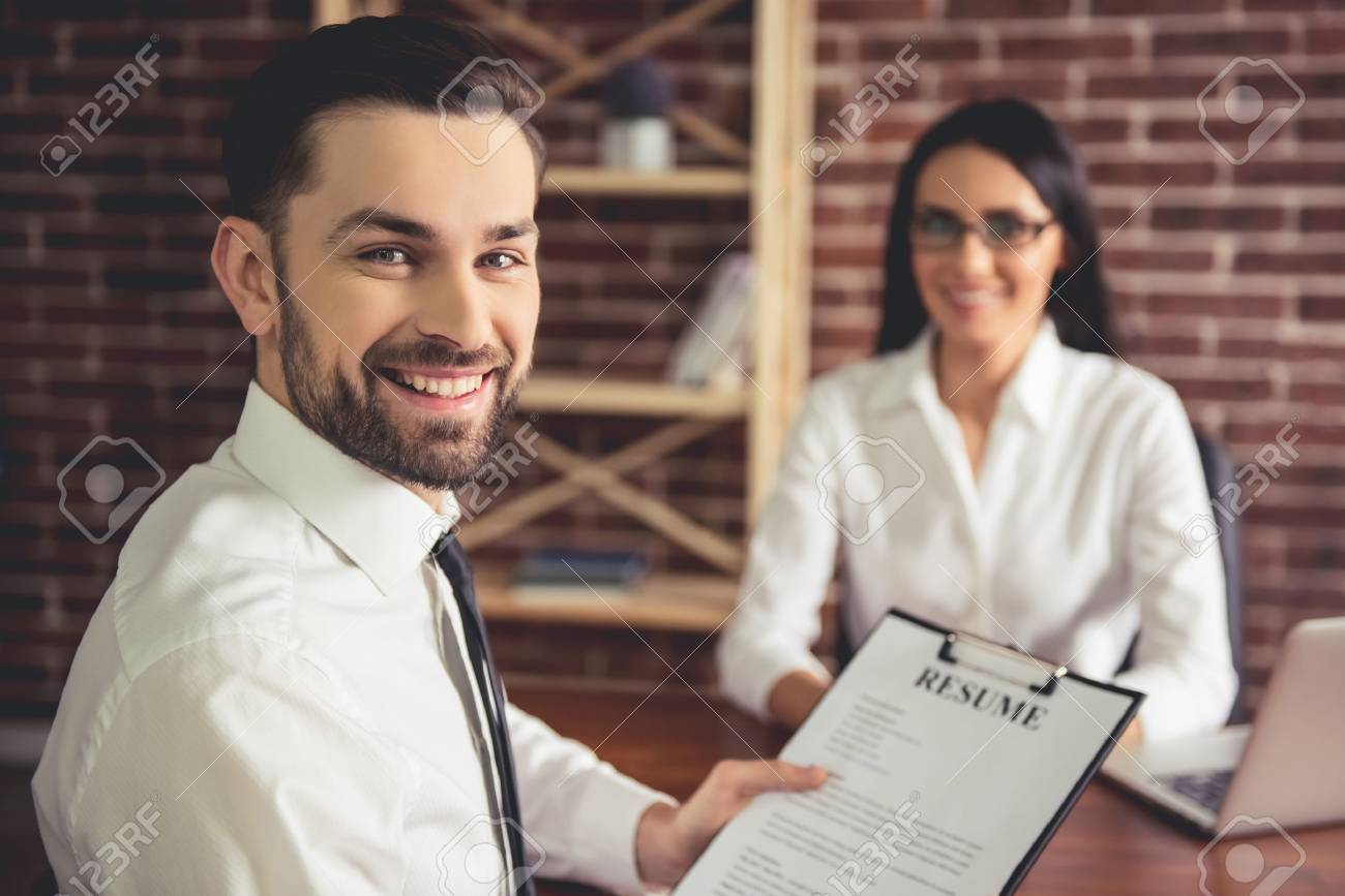 Handsome employee in suit is holding a resume, looking at camera and smiling during the job interview - 72680710