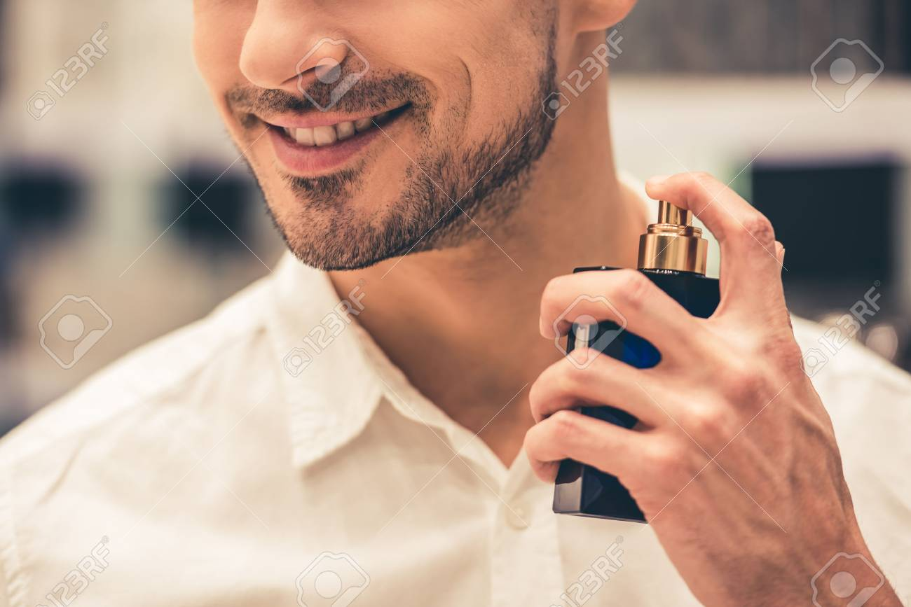 Handsome guy is choosing perfumes and smiling while doing shopping in the mall - 74025283