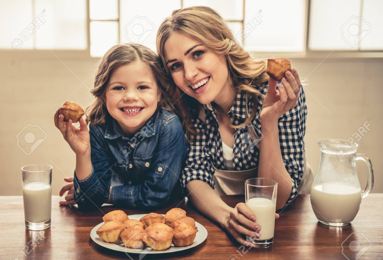Cute little girl and her beautiful young mom are eating muffins with milk, looking at camera and smiling while resting at home - 74330070