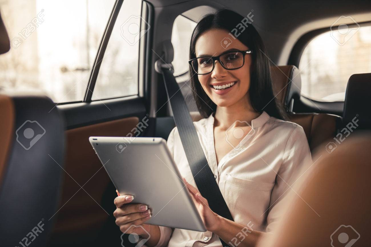 Beautiful business woman in eyeglasses is using a digital tablet and smiling while sitting on back seat in the car - 75068380