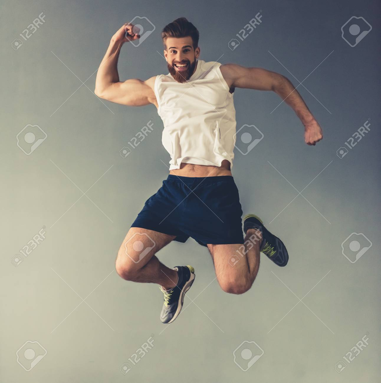 Handsome young bearded sportsman is showing muscles, jumping and smiling, on gray background - 79241600