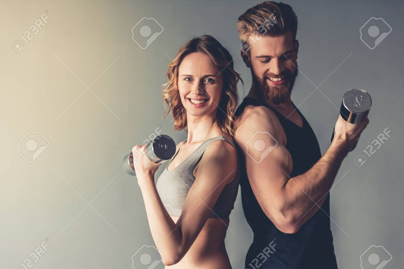 Beautiful young sports people are working out with dumbbells and smiling, on gray background - 79149180