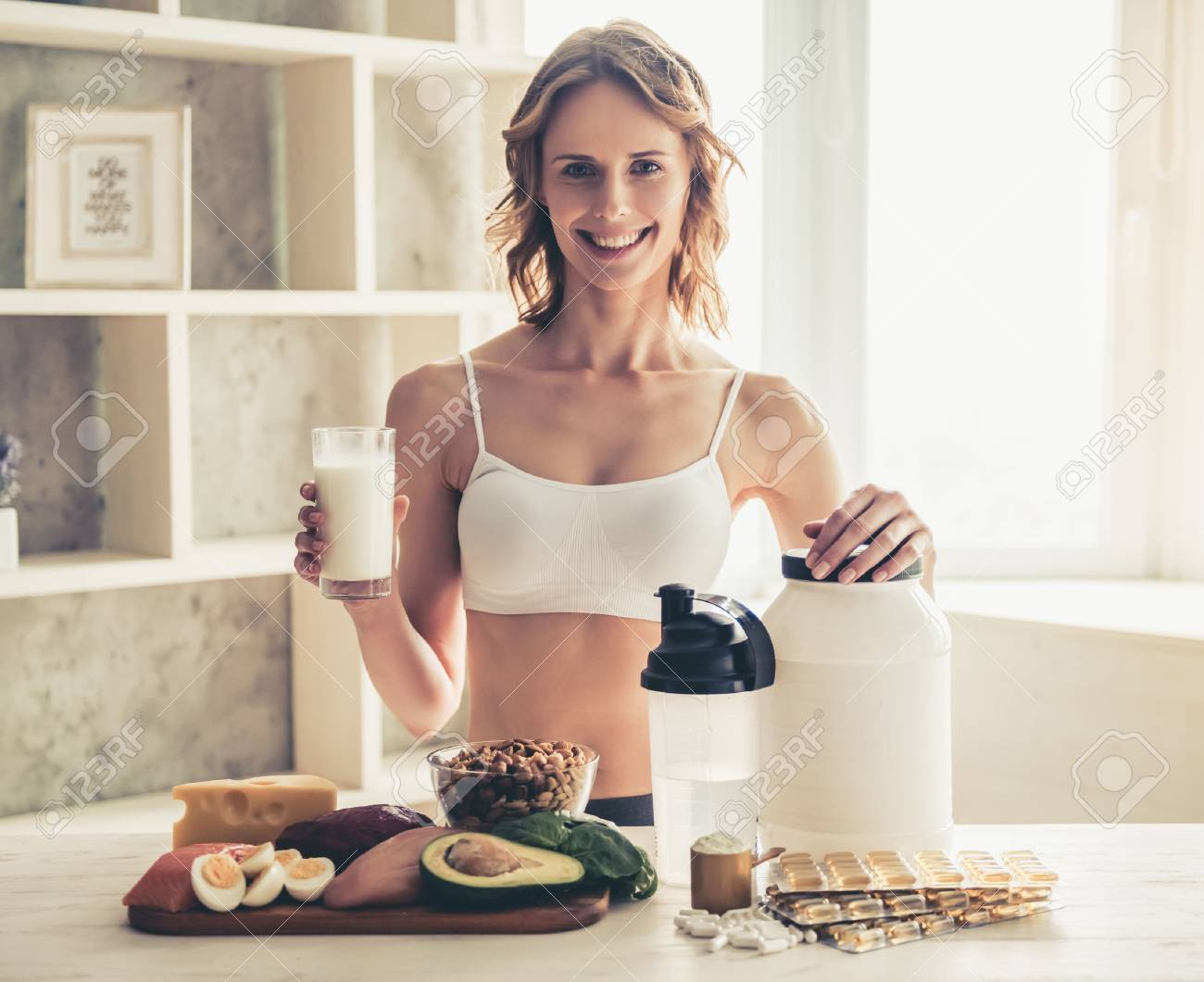 Beautiful young sportswoman is looking at camera and smiling while preparing sport nutrition in kitchen at home - 79149197