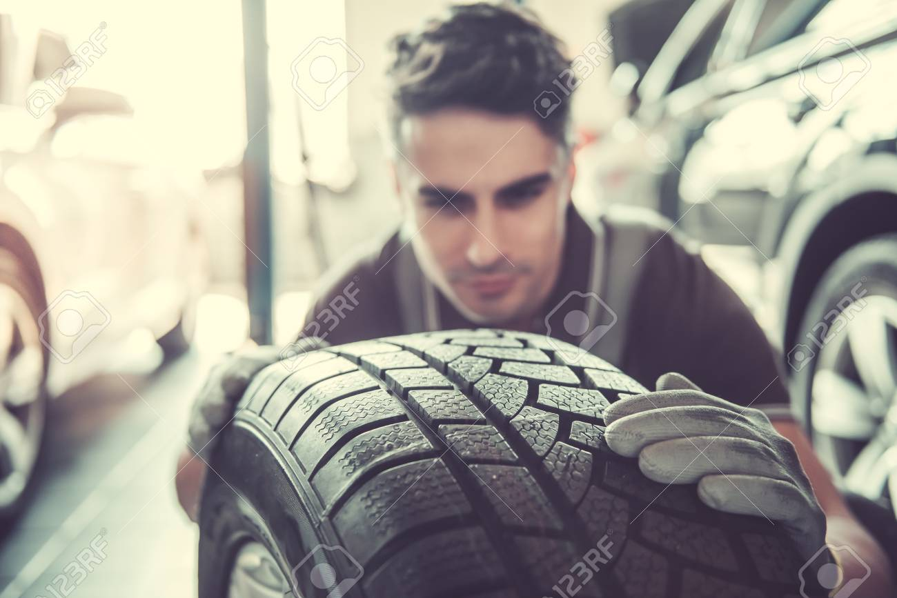 Handsome young auto mechanic in uniform is examining a tire while working in auto service - 76956044