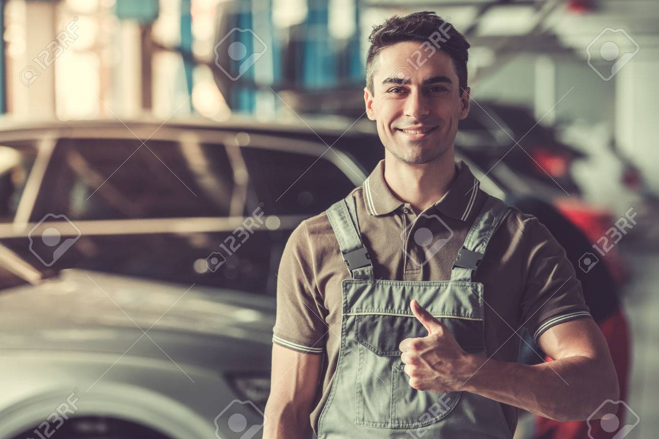 Attractive young auto mechanic in uniform is showing Ok sign, looking at camera and smiling while standing in auto service - 76956058