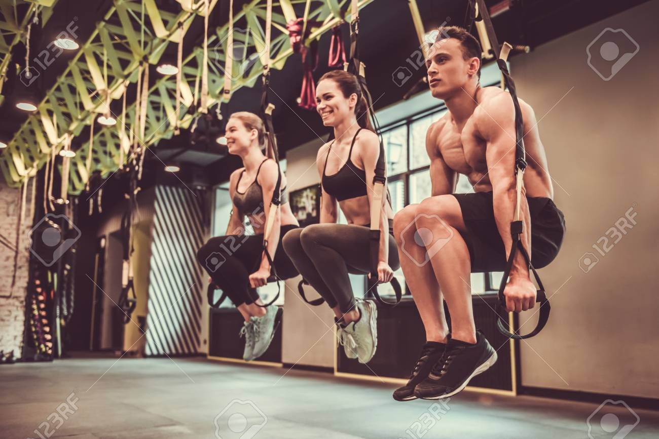Beautiful young sports people are working out with TRX in gym - 77194217