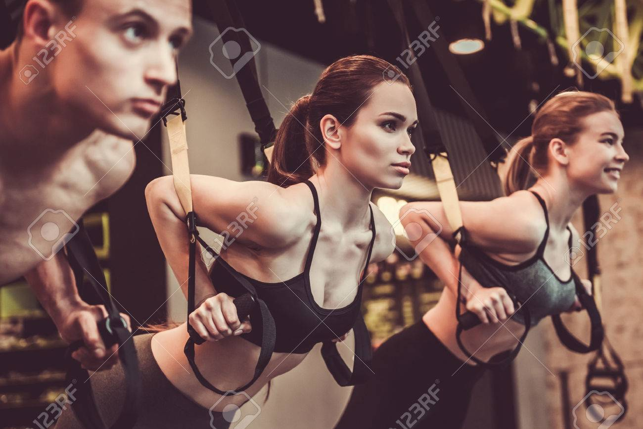 Beautiful young sports people are working out with TRX in gym - 77194221