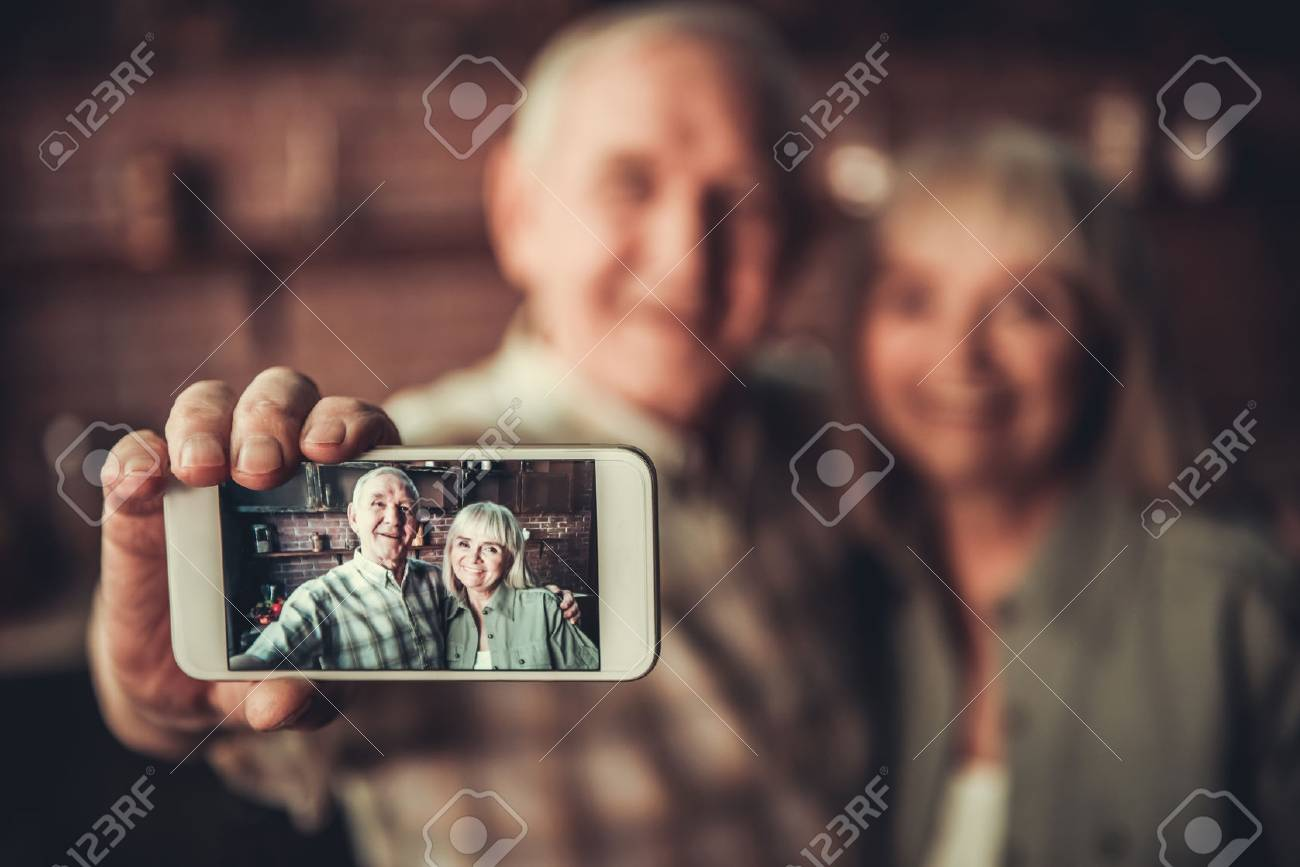 Beautiful senior couple is hugging, doing selfie using a smart phone and smiling while standing in kitchen. Phone in focus - 79737445