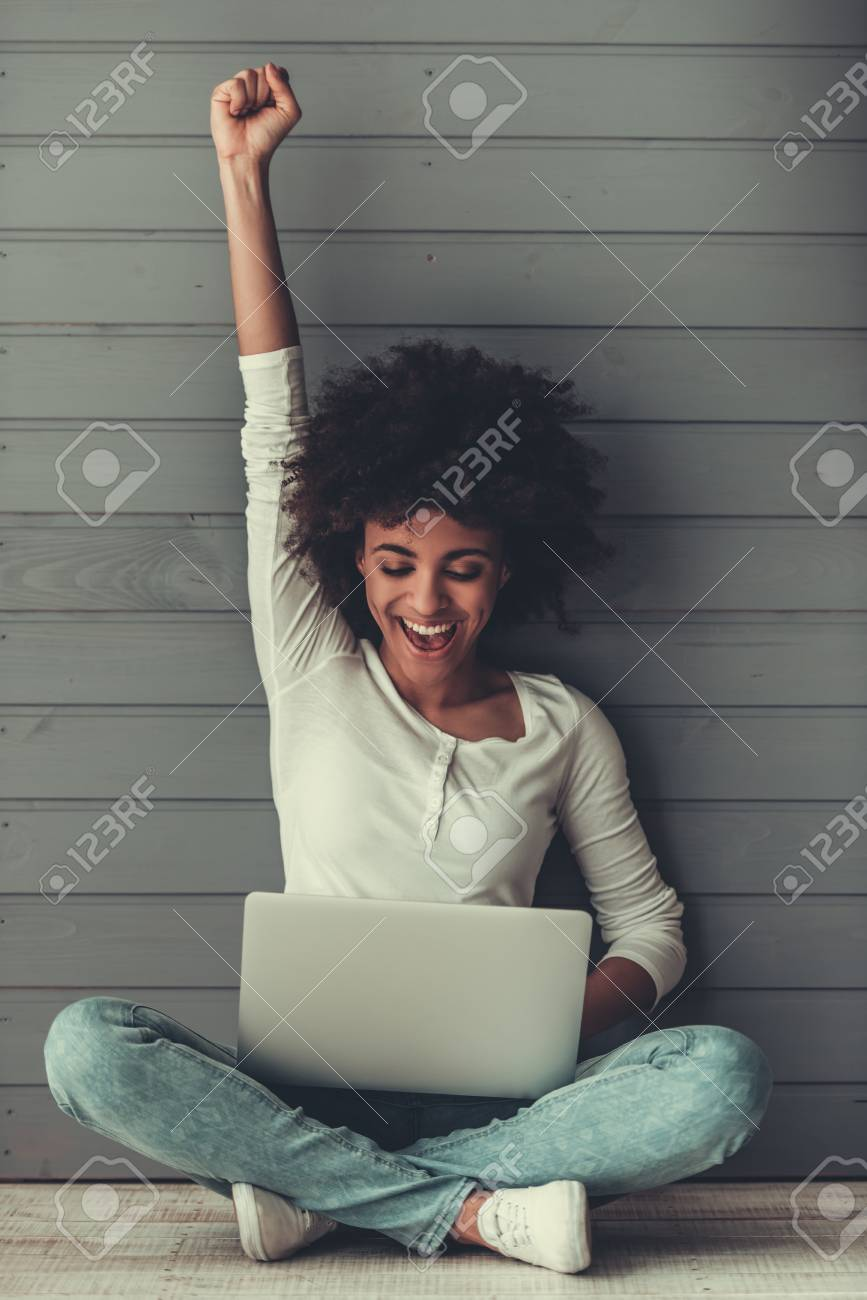 Attractive Afro American girl is using a laptop, raising hand in fist and smiling while sitting on the floor - 81369657