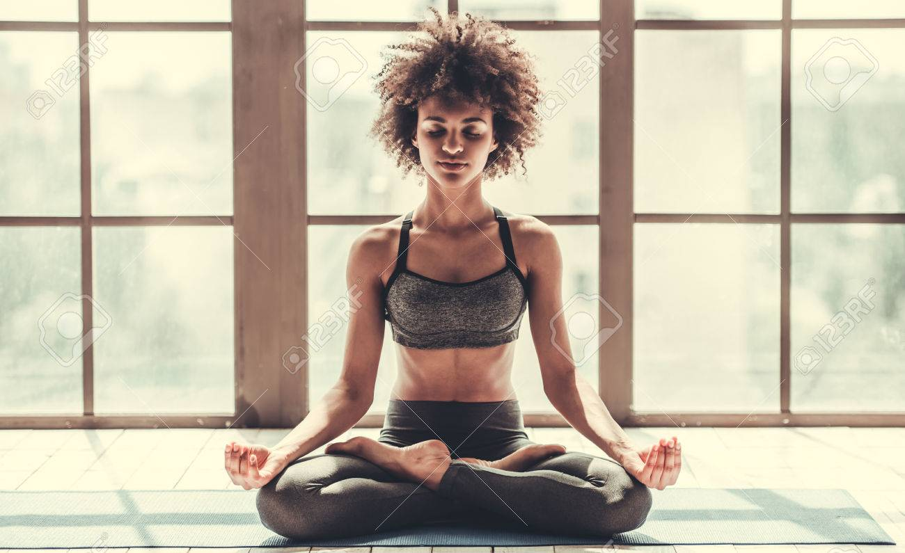 Attractive Afro American girl in sportswear is meditating while doing yoga - 81320057