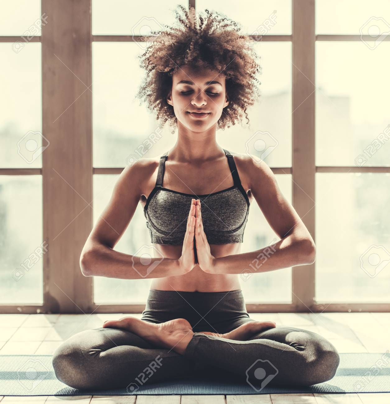 Attractive Afro American girl in sportswear is doing yoga and smiling - 81410831