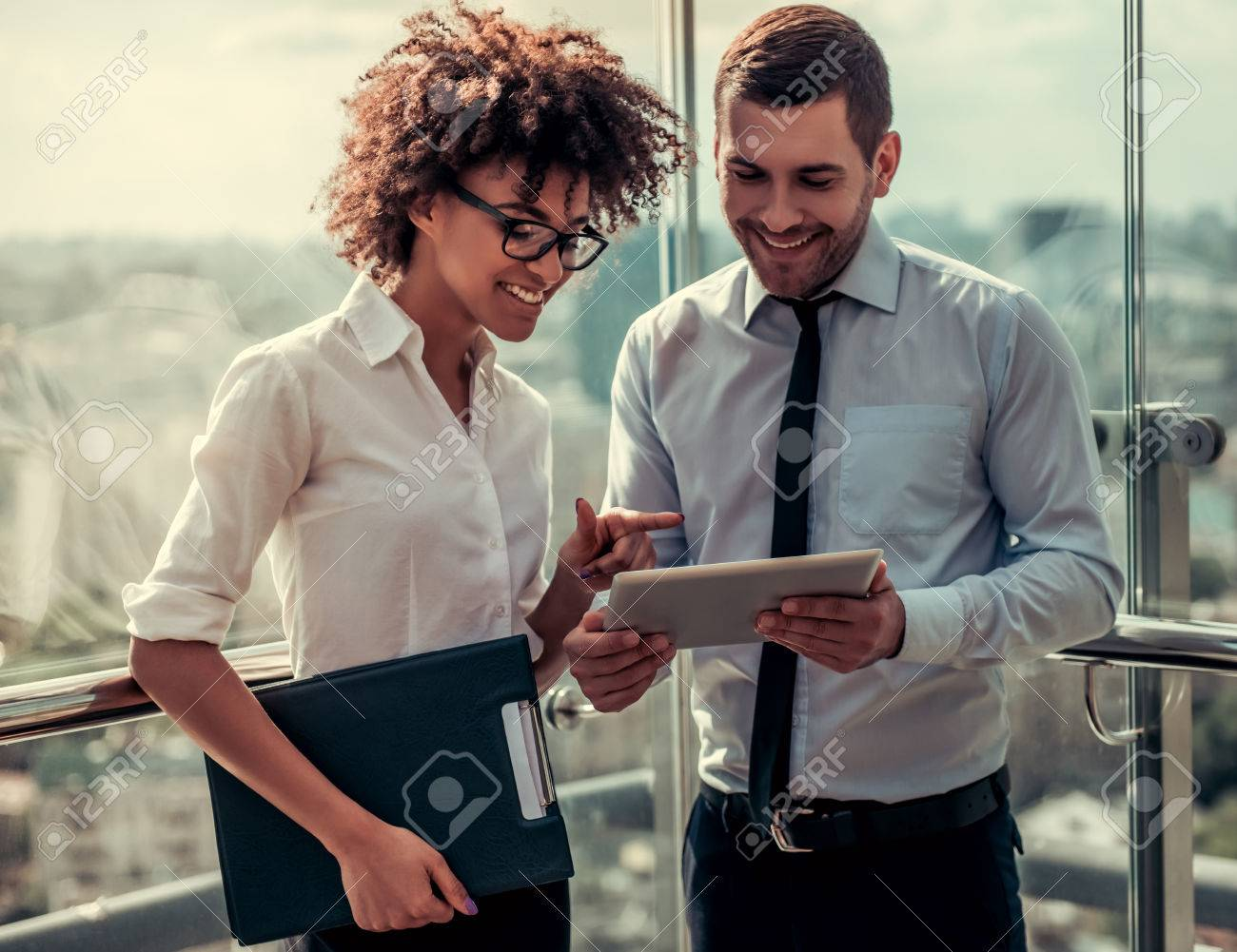 Handsome businessman and beautiful Afro American businesswoman are using digital tablet and smiling while standing on balcony of the office building - 83087621