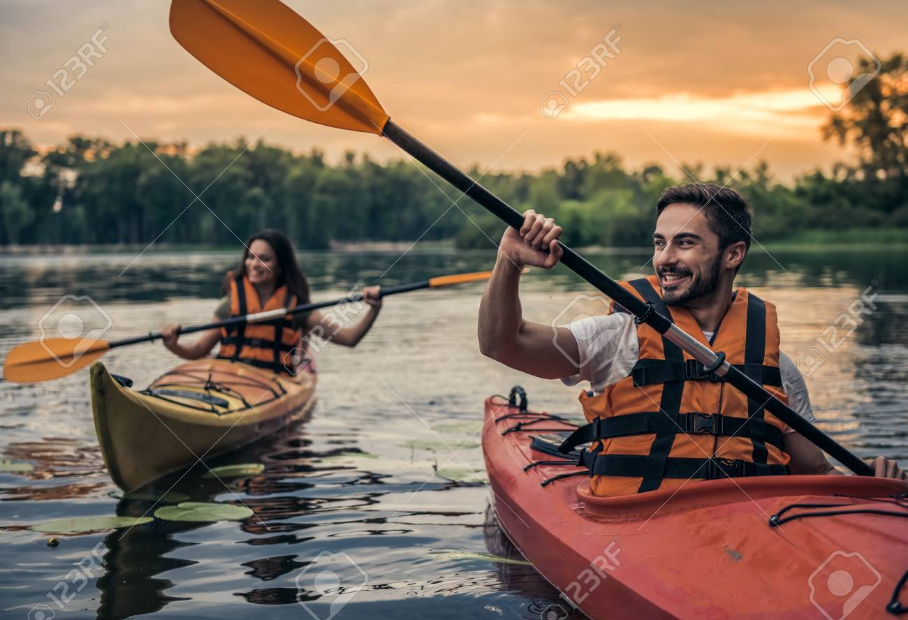 Happy young couple in sea vests is smiling while sailing kayaks - 83936595